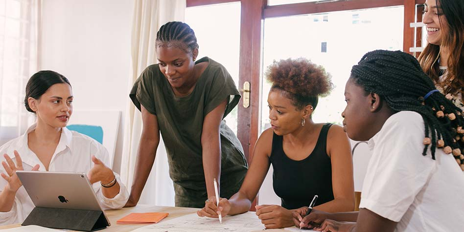 a diverse group of women gathered around a table at a business strategy session