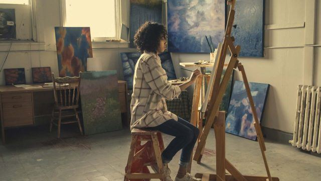 a woman painting calmly on a easel in an art studio