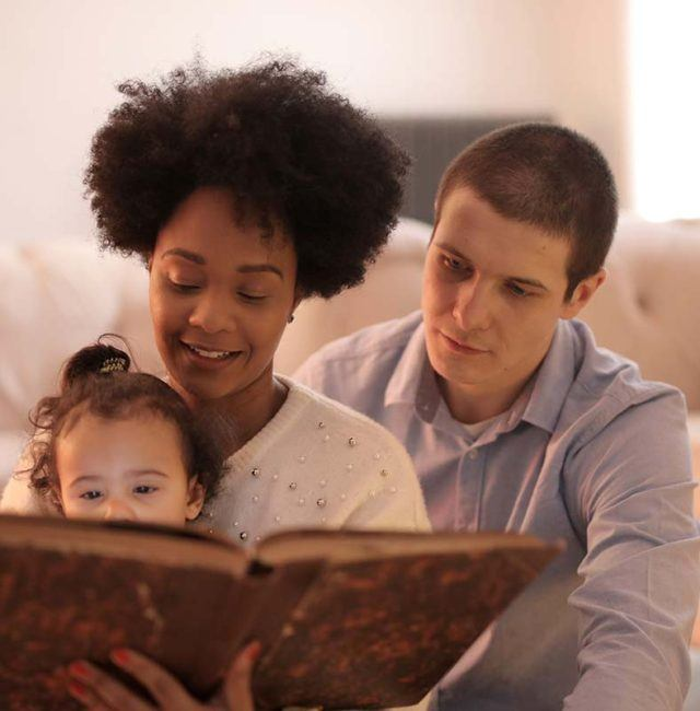 a mother and father reading a book to their young daughter