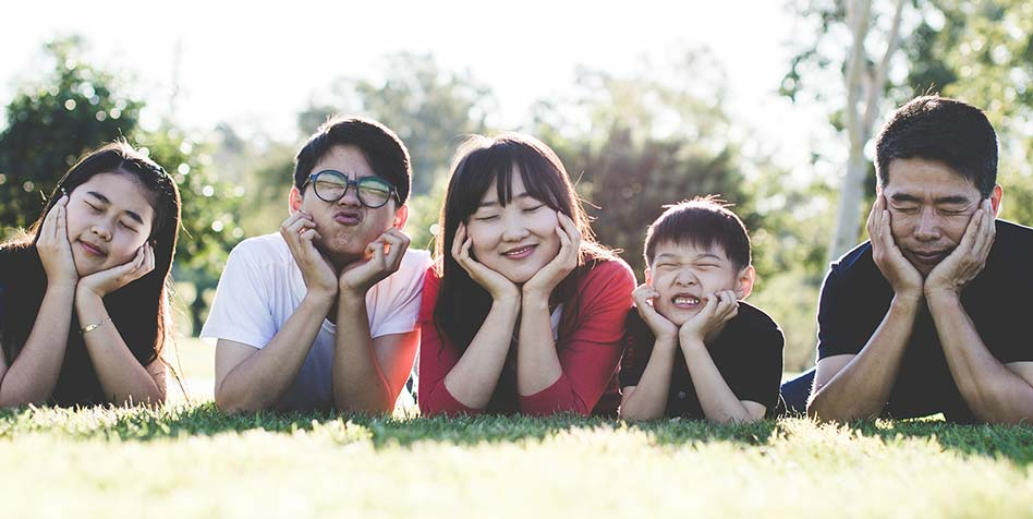 a Asian family posing on the grass on a sunny day taking a family photo and making funny faces