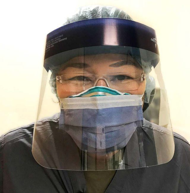 a female healthcare professional wearing a medical mask and a face shield