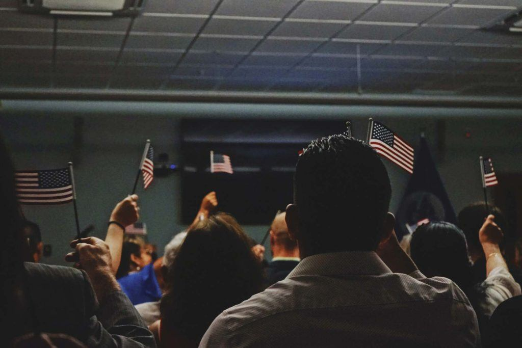 people holding up USA flags at an immigration ceremony