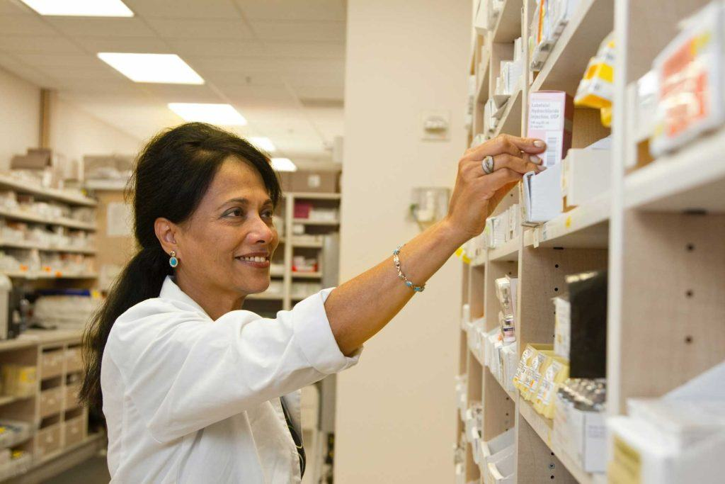 a female pharmacist in a pharmacy checking the stock on a shelf